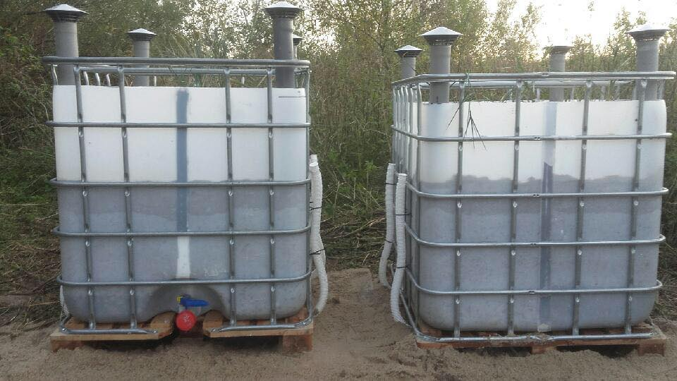 Two plastic tanks in metal cages on the outside.